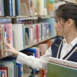 Woman looking for books from shelf — Stock Photo #36135827