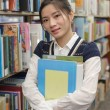 Young student holding books near bookshelf — Stock Photo