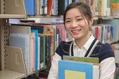 Young student holding books near bookshelf — Stock Photo