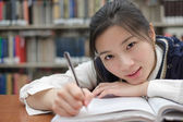Tired student doing homework in library — Stock Photo