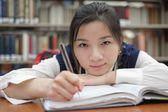 Tired student doing homework in library — 图库照片