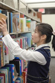 Woman taking a book from library shelf — Stock Photo