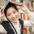 Girl holding a book over head near bookshelf — Stock Photo