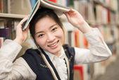 Girl holding a book over head near bookshelf — Stock Photo