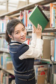 Woman taking a book from a bookshelf — Stock Photo