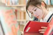 Student reading a book on bookshelf — Foto Stock