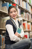 Girl huggering a book near bookshelf — Stock Photo