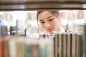 Woman looking for book from bookshelf — Foto de Stock