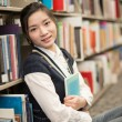 Stock Photo: Girl huggering book near bookshelf