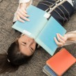 Student laying on carpet with books — Stok fotoğraf