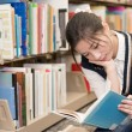 Woman reading a book near bookshelf — Stock Photo