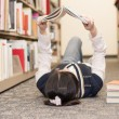 Stock Photo: Student laying on floor reading book