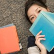 Student laying on carpet with books — Stock Photo