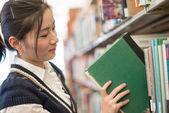 Woman putting book back onto a bookshelf — Stock Photo