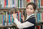 Portrati of student in front of bookshelf — Stock Photo