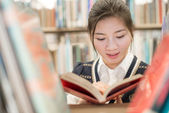 Student reading a book on bookshelf — Foto de Stock