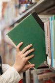 Student putting book back onto a bookshelf — Stock Photo