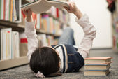 Student laying on floor reading book — Stockfoto