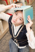 Girl holding a book over head near bookshelf — Stockfoto