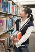Woman holding books next to bookshelf — Stock Photo