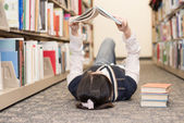Student laying on floor reading book — Stock Photo
