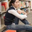 Student next to bookshelf looking depressed — Stock fotografie