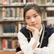 Student studying at a desk in library — Stock Photo