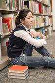 Student next to bookshelf looking depressed — Stock Photo