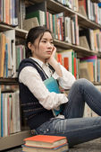 Student next to bookshelf looking depressed — Stockfoto