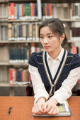 Stressed student sitting at a desk in library — Stock Photo