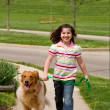 Stock Photo: Young Girl Walking Dog