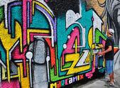Colourful graffiti spraying artist on the street — Stock Photo