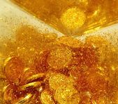 Gold sand and gold coins — Stock Photo