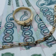 Stock Photo: Golden bracelet and ring on rubles