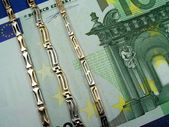 Golden bracelets and money — Stock Photo