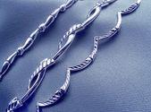 Bracelets on grey silk — Stock Photo