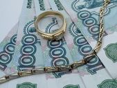 Golden bracelet and ring on rubles — Stock Photo