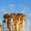 Golden fountain on blue sky — Stock Photo