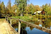 Wooden old bridge and houses in country — Stock Photo