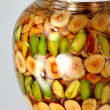 Nuts in honey in glass — Stock Photo