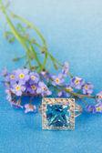 Elegant jewelry and blue flowers — Stock Photo