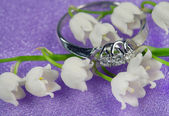 Elegant jewelry and lily of the valley — Stock Photo