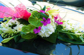 Blossom flowers on wedding automobile — Stock Photo