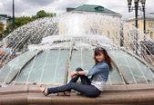 Dívka pózuje u fontány — Stock fotografie