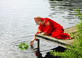 Woman in National suit sending wreath in river — Stock Photo