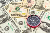 Compass on a heap of paper dollars. — Stock Photo
