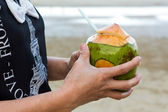 Woman hand holding coconut. — Stock Photo