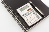 Calculator with notebook & pen — Stock Photo
