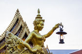 Goldent Ginnaree statue art holding a lamp. — Stock Photo