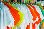 Variety of multicolored shirt clothes hangers in row. — Stock Photo